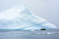 One of our zodiacs passes by an iceberg. Look at the size of that 'berg!