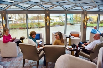 Back on board ship, some of our gang relax and watch the scenery go by as we sail up the river