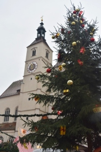 The church in the square with one of the Christmas trees set up for the markets